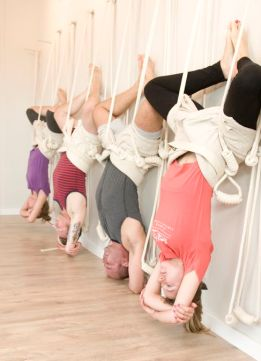 yoga students hanging upside down in ropes