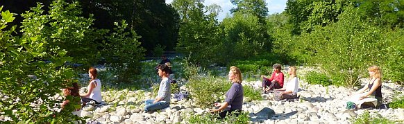 People meditating next to a river.