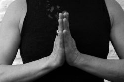 woman holding hands together in yoga posture